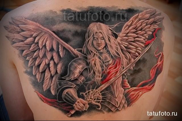 Татуировка ангел с мечом выполненная между лопатками