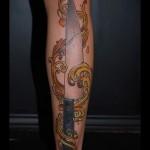 большая татуировка на ноге с рисунком ножа в огне