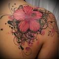 большой и яркий цветок в тату на лопатке