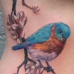 ветка цветов и маленькая цветная птичка - женская татуировка на боку