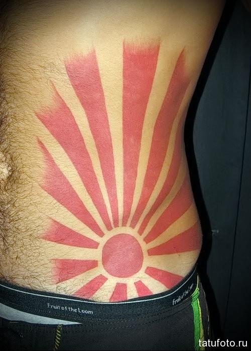 восходящее солнце в тату на боку у мужчины