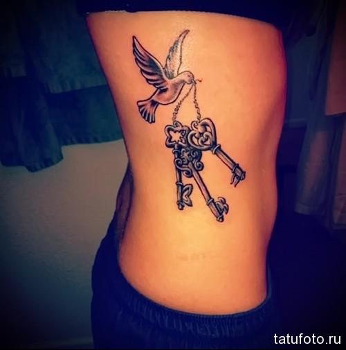 голубь с ключами в клюве - женская татуировка на боку