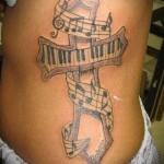 ерест из клавишей от пианино и ноты - женская татуировка на боку