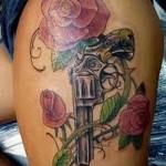 женская тату с револьвером и цветами роз на ногу сбоку
