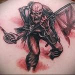 зомби с саблей и флагом на поле боя - тату мужская на спине фото