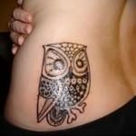 крупная сова - женская татуировка на боку