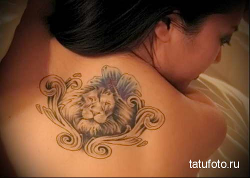 лев и вензеля в рамке тату на спине женская