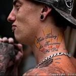 лучи восходящего солнца и надписи - татуировка на шее мужчины - фото
