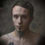 молодой парень с татуировками на лице
