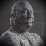 мужчина с татуировками на все лицо и тело
