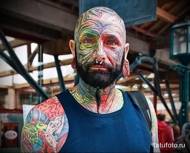 мужчина с цветными тату на лице