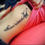 надпись в строчку и птички - женская татуировка на боку