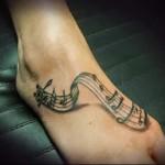 нотный стан с нотками - татуировка на стопе мужская - фото