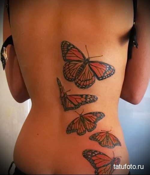 оранжевые бабочки в полете тату на спине женская