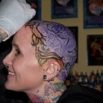 процесс нанесения татуировки в цвете на голову девушке