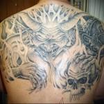 рогатый демон в аду и черепа - тату мужская на спине фото