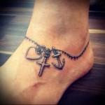 татуировка браслет с разными кулончиками внизу ноги девушки