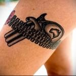 татуировка маленький револьвер и подвязка на ноге для девушки