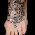 татуировка мандала внизу ноги девушки