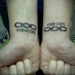 татуировка с цепями и надписями на запястьях двух рук