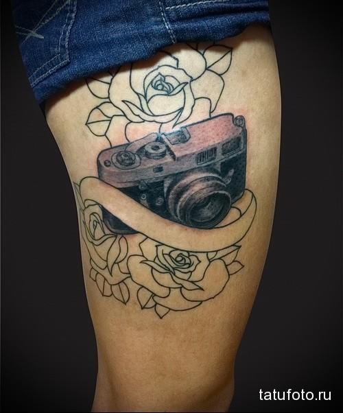 татуировка фотоаппарат и лента под надпись с цветами на ногу для девушки