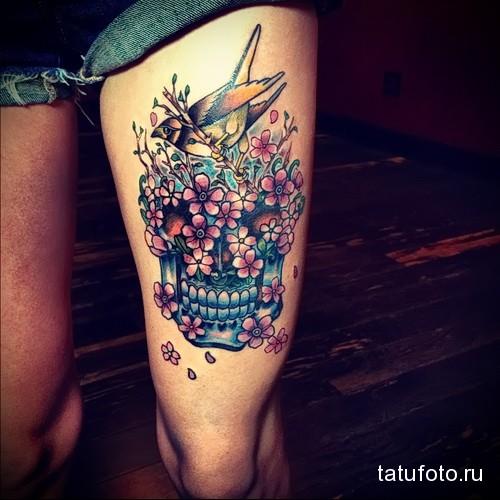 татуировка череп в цветах и маленькая птичка на ногу для девушки