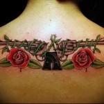 татуировка 2 револьвера на спине девушки и розы - фото