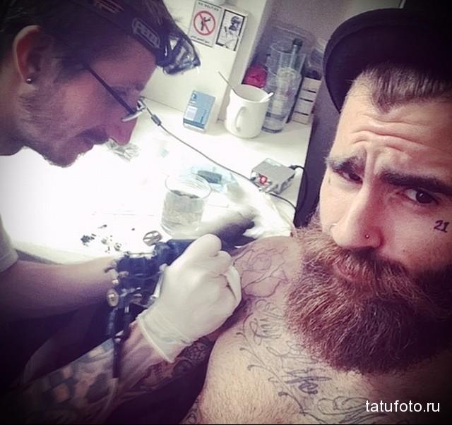 татуировка 21 под глазом парня