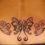 тату бабочка и цветки сакуры с завитками - татуировка на пояснице женская фото