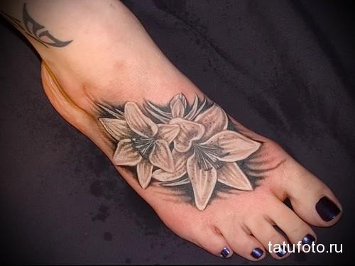 тату белые цветы внизу ноги девушки