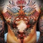тату корона, кисти, карандаши и крылья - мужская татуировка на грудь