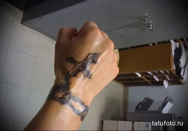 тату крест и браслет на руке парня