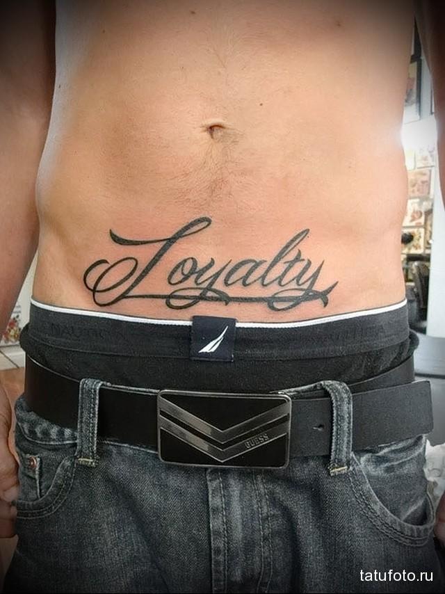тату на животе парня - крупная надпись
