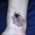 тату паутина и паук с красной точкой на попе - выполнена на запястье