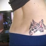 тату птичка с веточкой в клюве - татуировка на пояснице женская фото