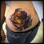 тату с бутоном розы на животе у девушки