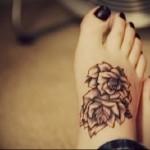 тату с тремя цветами внизу ноги девушки