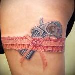 цветная татуировка револьвер и подвязка на правой ноге