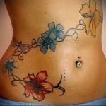 цветная татуировка с цветочками внизу живота девушки