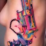 цветной пистолет (револьвер) - женская татуировка на боку