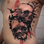 черепа и вороны в тату на боку у мужчины