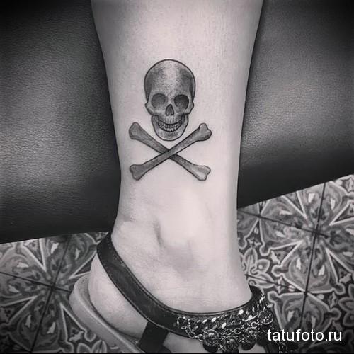 череп и кости в татуировка в нижней части ноги девушки