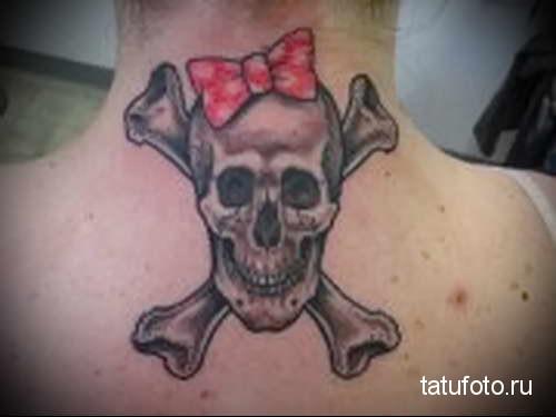 череп - кости и женский бантик - татуировка на шее женская - фото