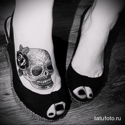 череп с цветком в волосах - татуировка в нижней части ноги девушки