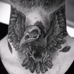 черный ворон и череп - татуировка на шее мужчины - фото