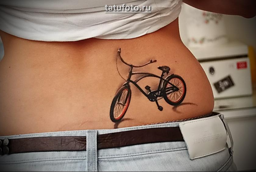 Татуировка с велосипедом на пояснице девушки