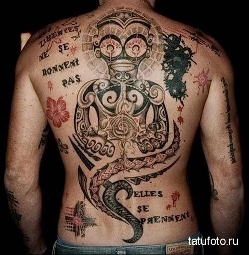 восточный идол и надписи - татуировка на спине мужская фото