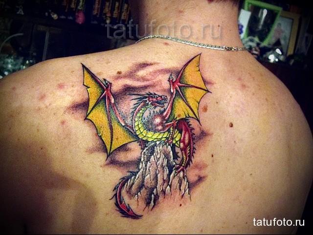 желто-красная татуировка с драконом на лопатке