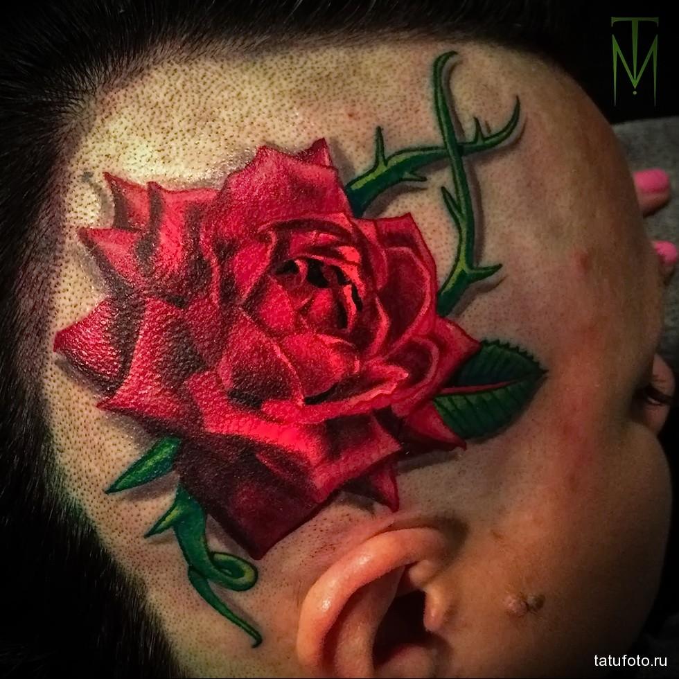 красная роза с шипами в женской татуировке на голове