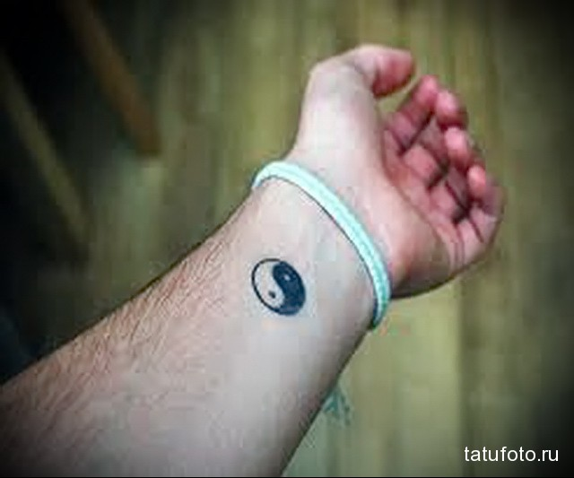 маленькая татуировка с символом инь-янь на запястье мужчины